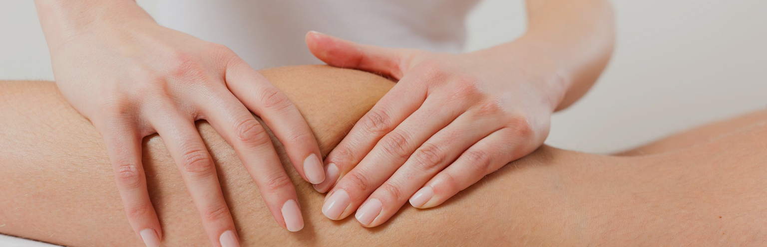 Qualified sports massage therapist works on a client's knee