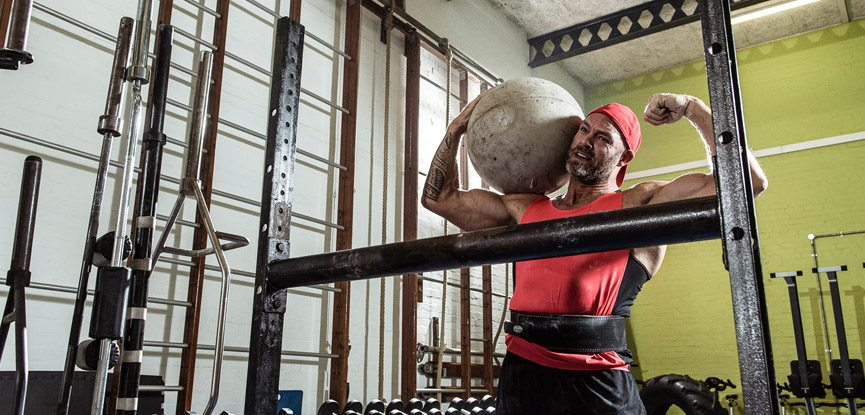 Former Gladiator James Crossley lifting an Atlas stone