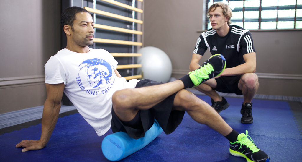 HFE personal trainer tutor working with a client on a foam roller