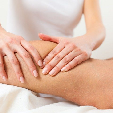 Sports massage therapist working on a client's knee