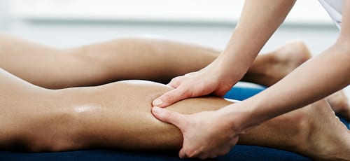 Qualified sports massage therapist working on the legs of an athlete client