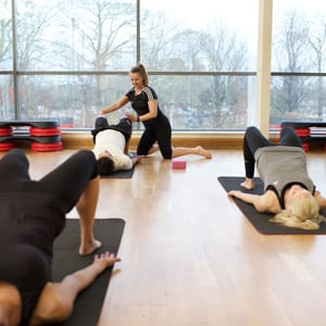 Qualified Pilates instructor assisting her the class with the bridge posture