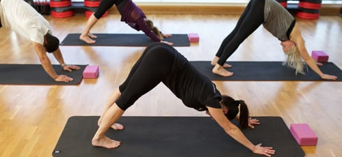 Yoga teacher performing downward-facing dog with her class