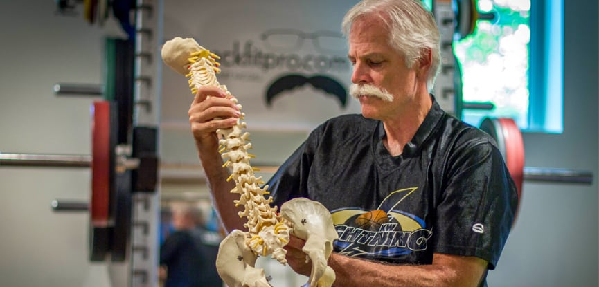 Professor Stuart McGill inspecting a model of a spine