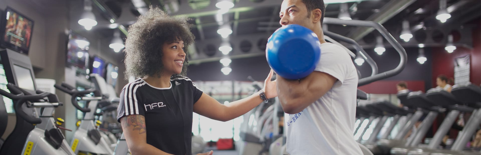 A qualified gym instructor working with a client