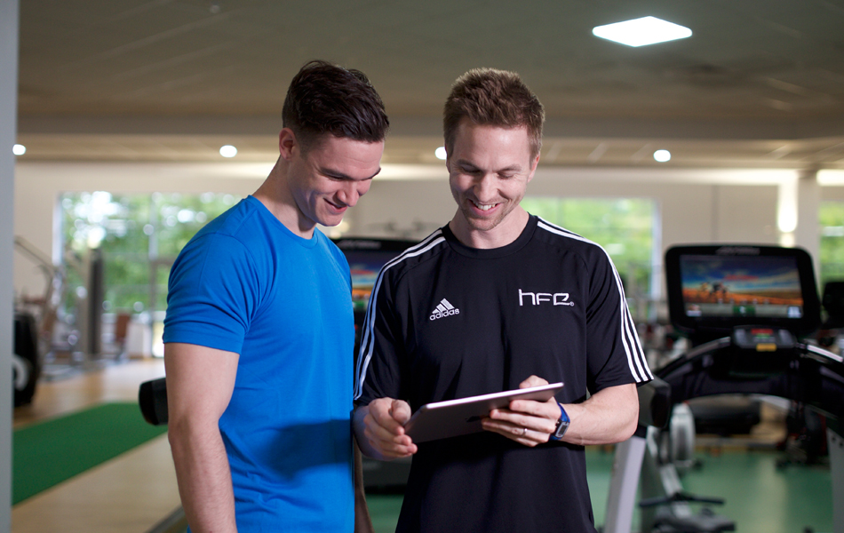 HFE tutor using an iPad with a student in a David Lloyd gym