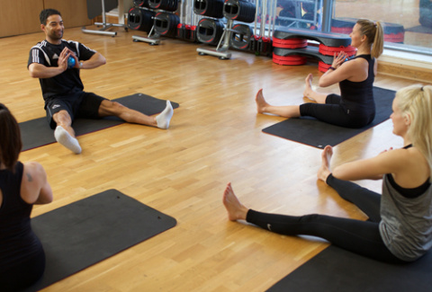 Pilates instructor leading a class with equipment