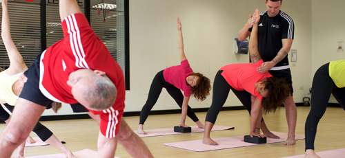 HFE yoga instructor correcting the revolved triangle pose