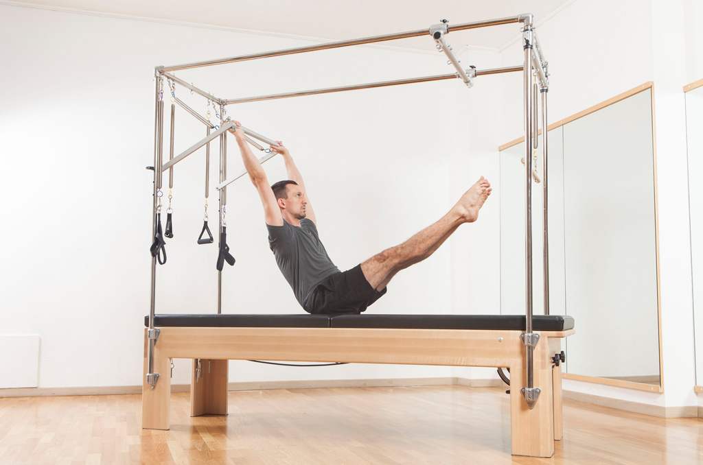 A man taking part in a Pilates class using a Cadillac