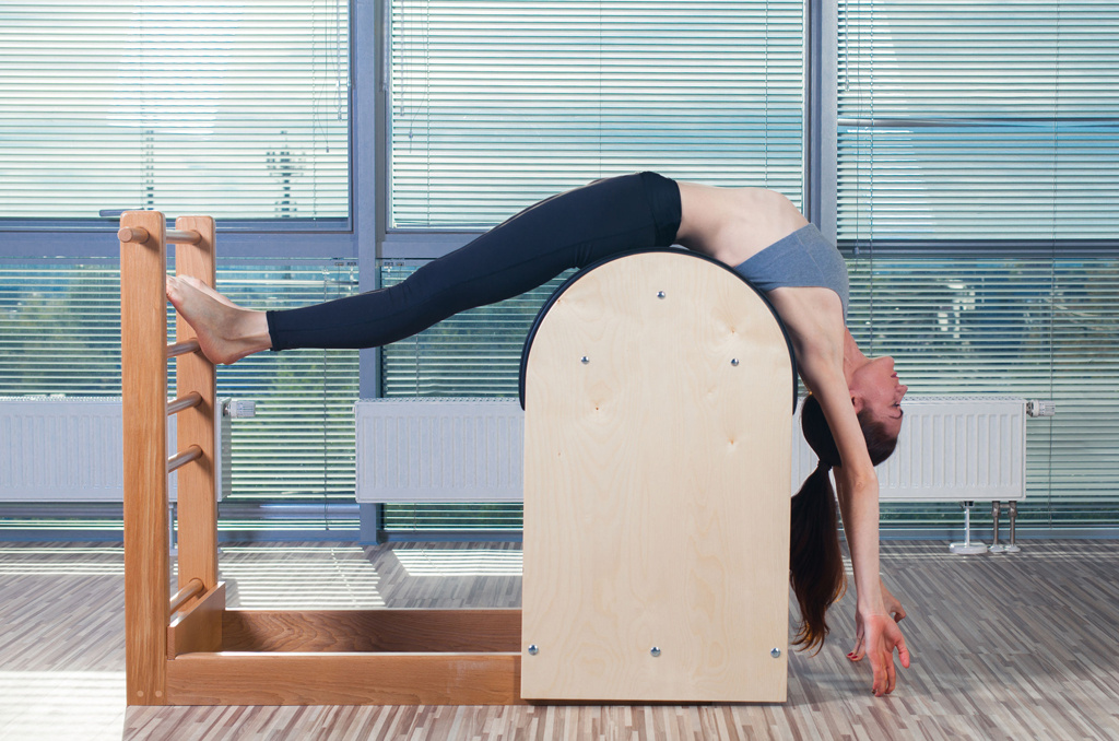 Female class participant using a ladder barrel in a Pilates class