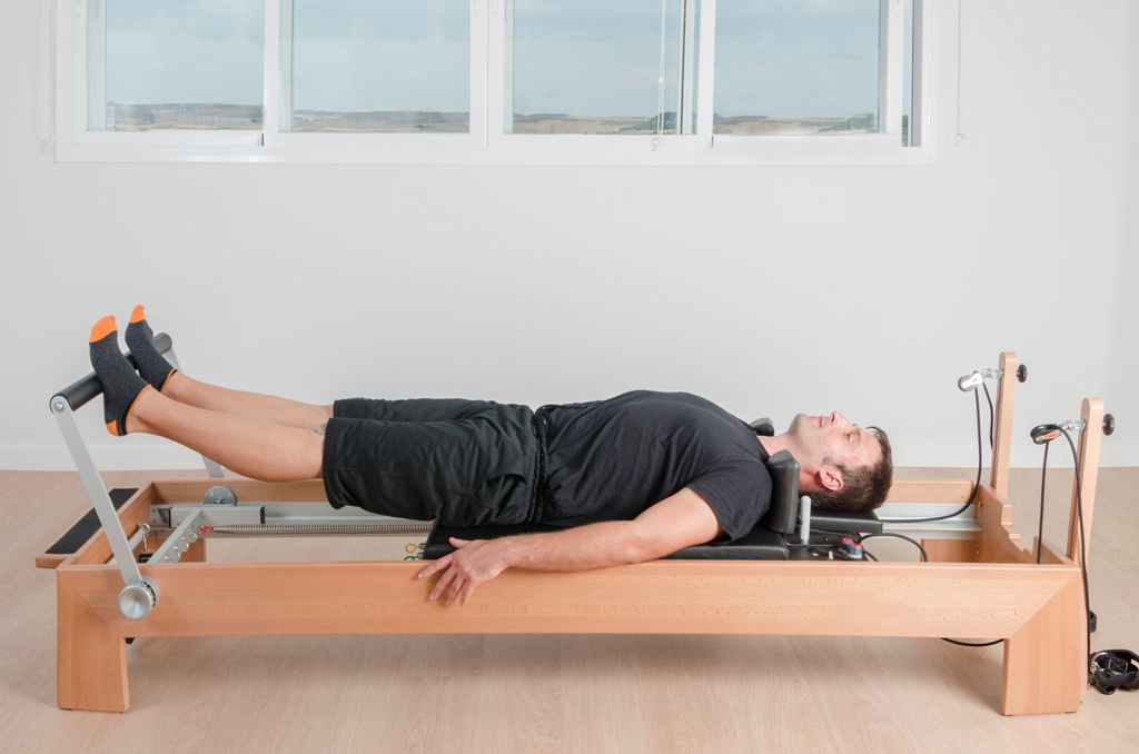 A class participant performing an exercise on a Pilates reformer
