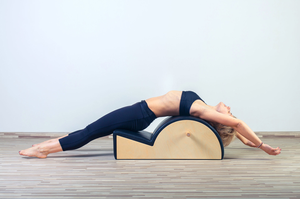 Female class participant using a spine corrector in a Pilates class