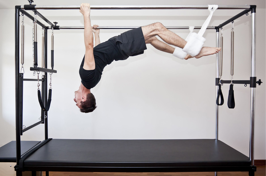 A man using the Trapeze, a specialised piece of Pilates equipment
