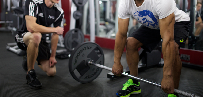 A personal trainer watching a client prepare for a deadlift
