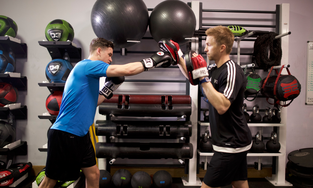 HFE personal trainer using boxing pads with a student