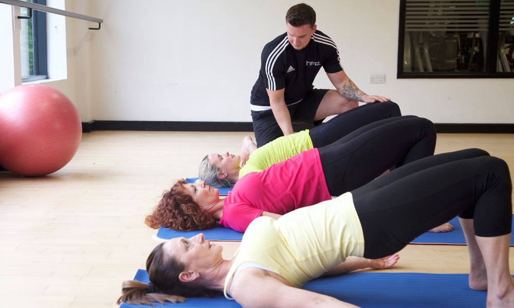 HFE Pilates instructor working with a class of students