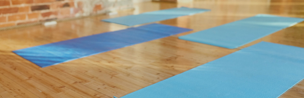 An empty yoga studio with blue mats arranged on the floor