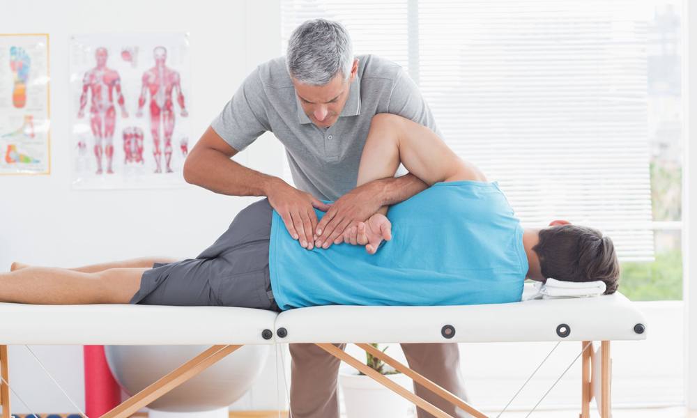 An exercise specialist instructor working with a client who has low back pain