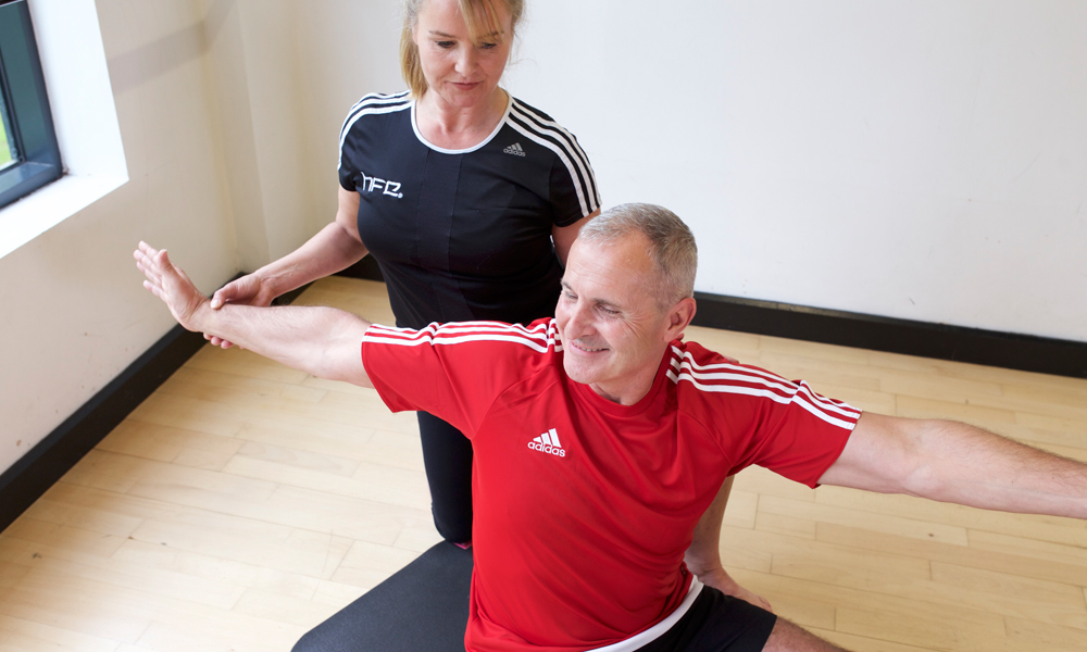 HFE Pilates instructor with working an older student