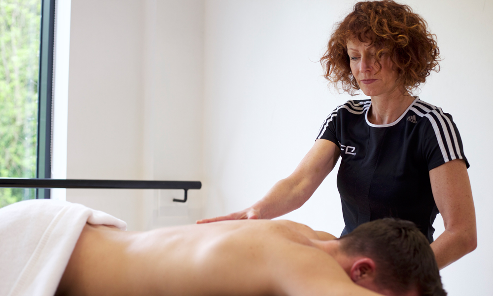 HFE sports massage therapy tutor demonstrating techniques on a client