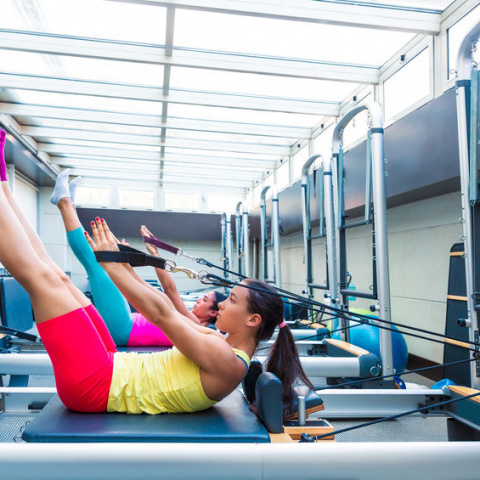 Reformer Pilates students practising an exercise