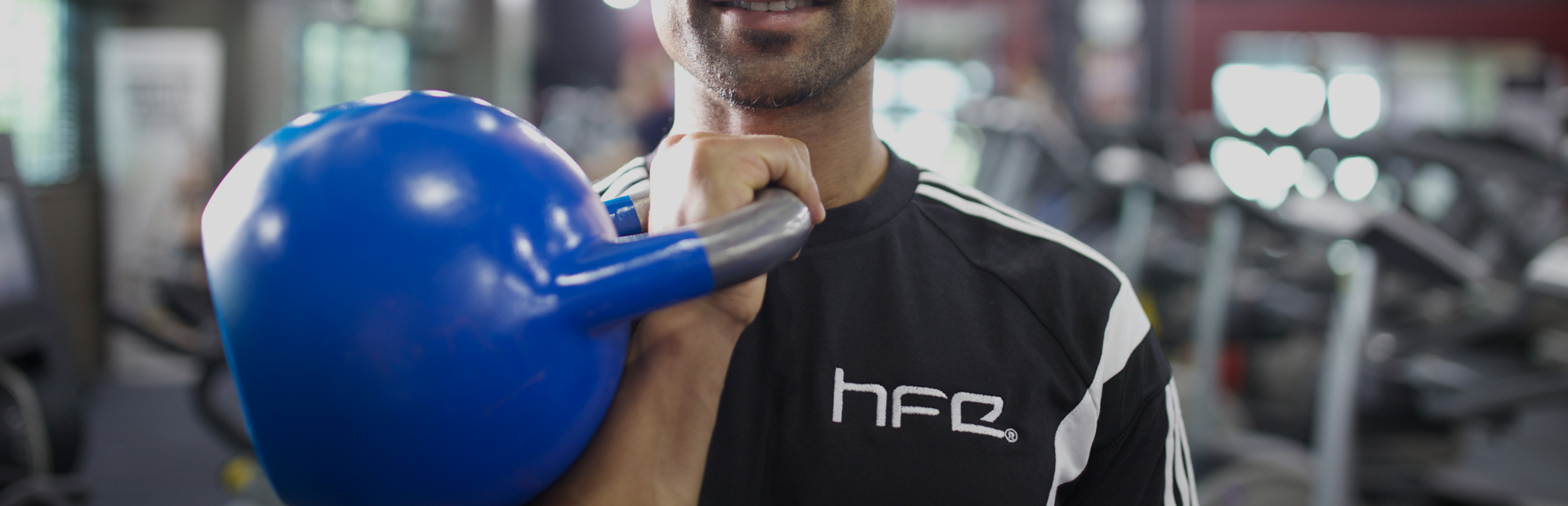 A qualified personal trainer holding a blue kettlebell