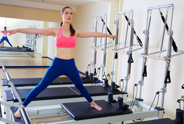 HFE student standing on a Pilates reformer