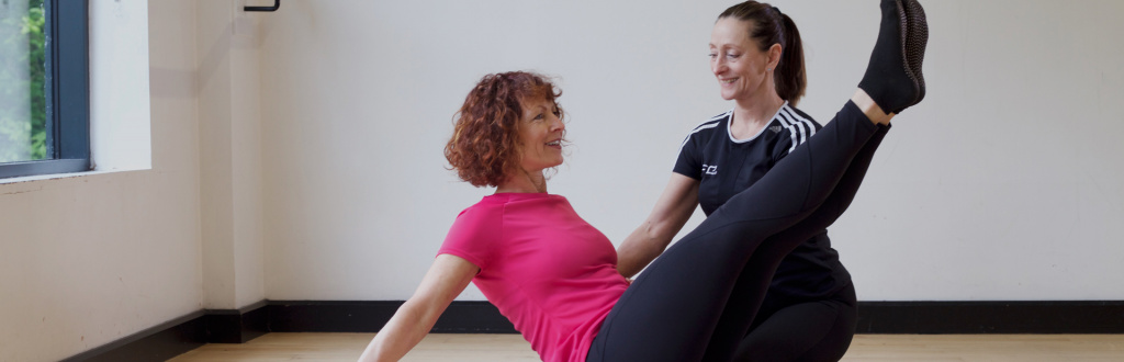 Student performing boat pose with a Pilates instructor