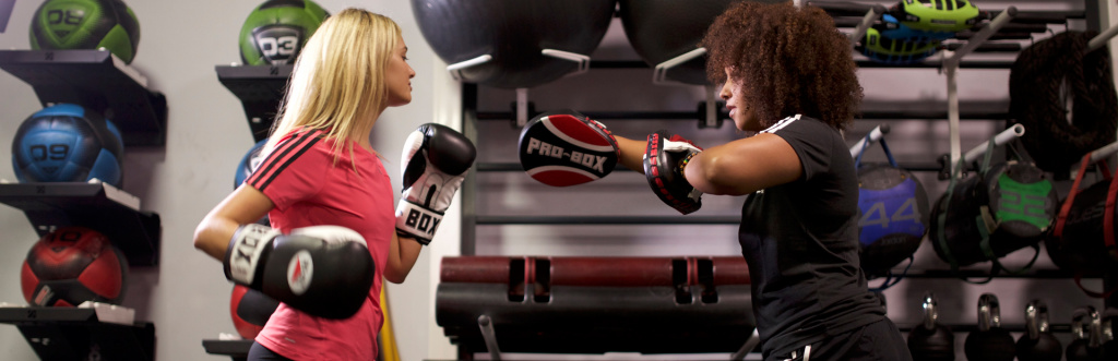 Personal trainer using boxing pads and gloves with a client