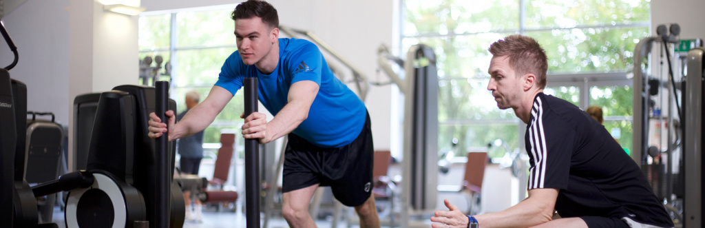 HFE personal trainer tutor working a student on a prowler
