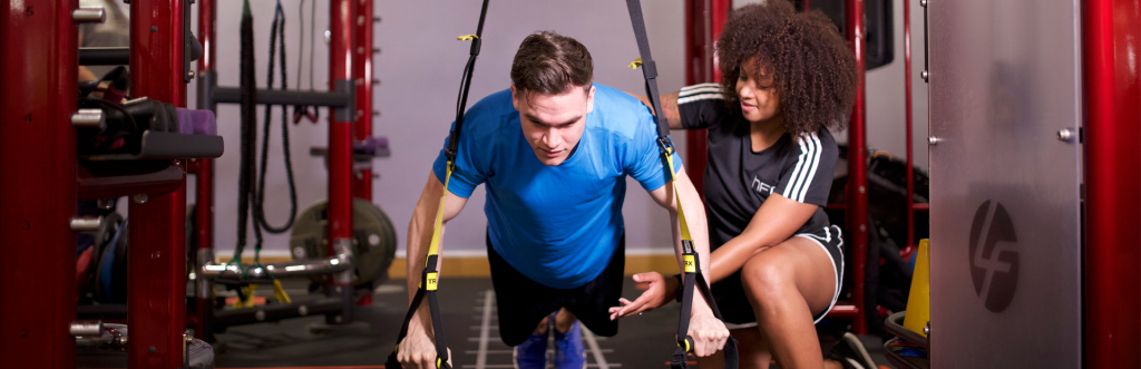 HFE personal trainer tutor working with a student on TRX