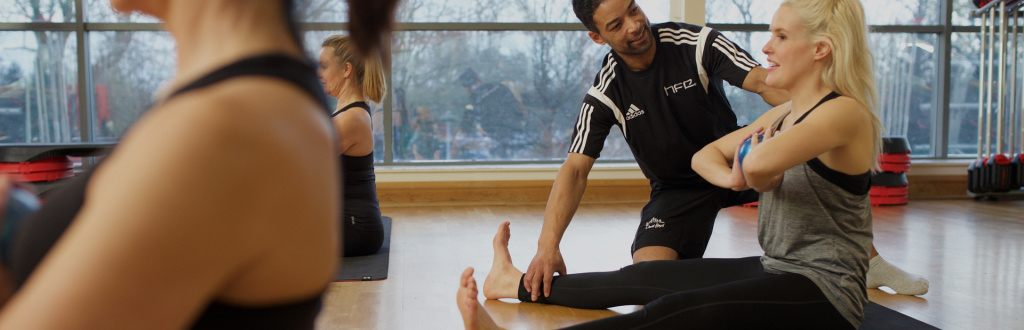HFE Pilates instructor working a student on her posture