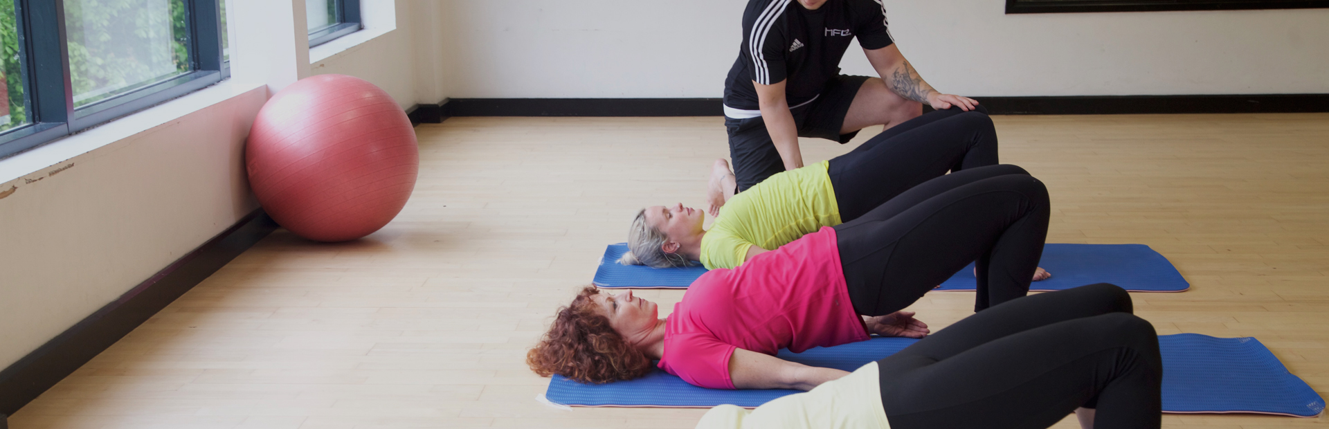 HFE Pilates tutor working on the bridge pose with students