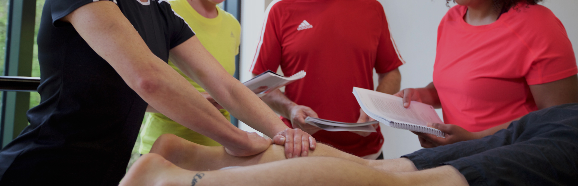 HFE sports massage tutor leads a hand-on session with students