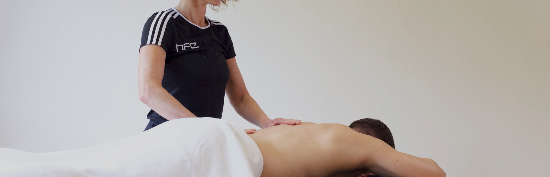 HFE qualified sports massage therapist working on a client