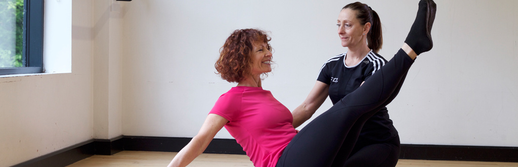 HFE Pilates instructor working with a student on boat pose