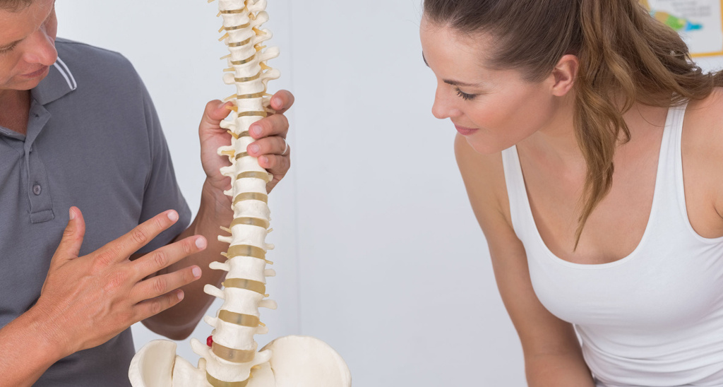 Exercise specialist showing a client a model of a spine