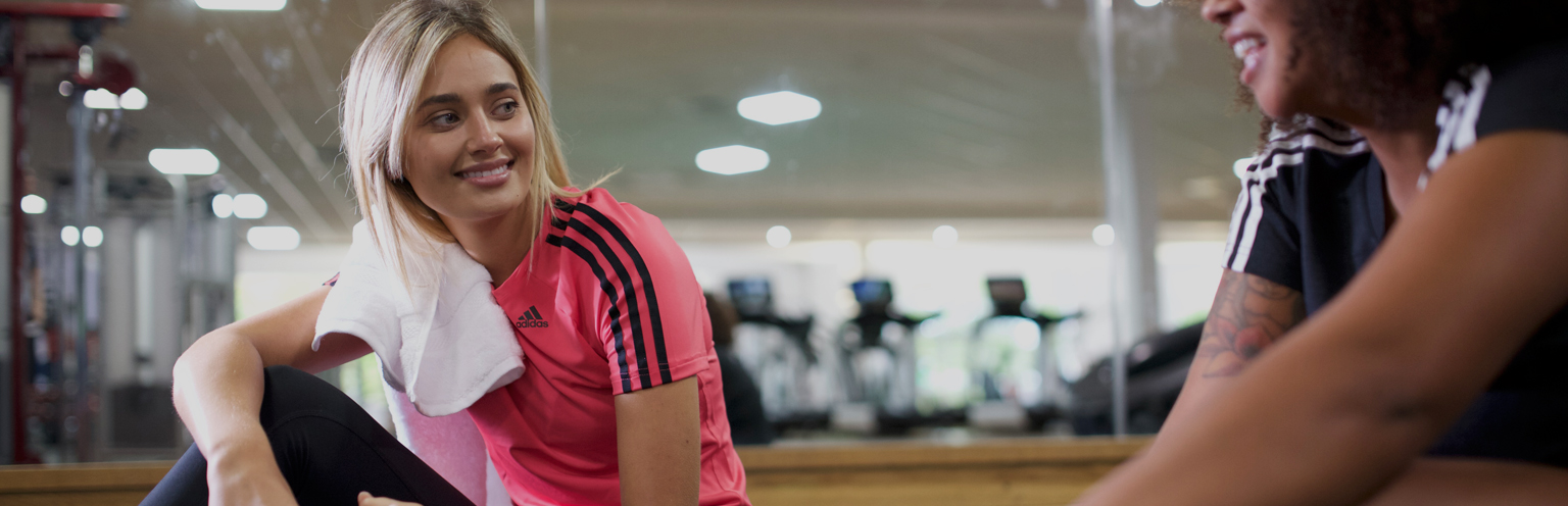Girl in gym sat listening to tutor