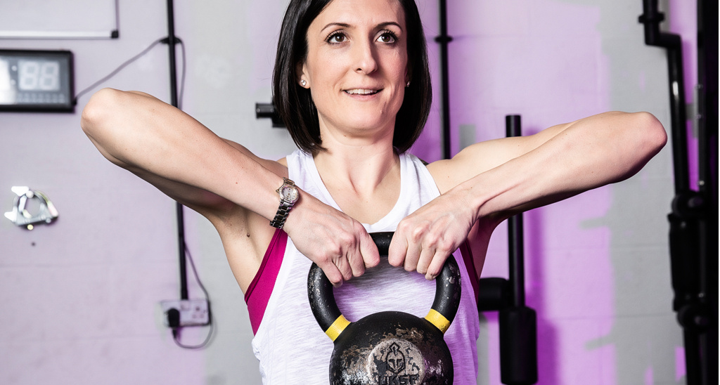 Personal training graduate Laura McNally lifting a kettlebell