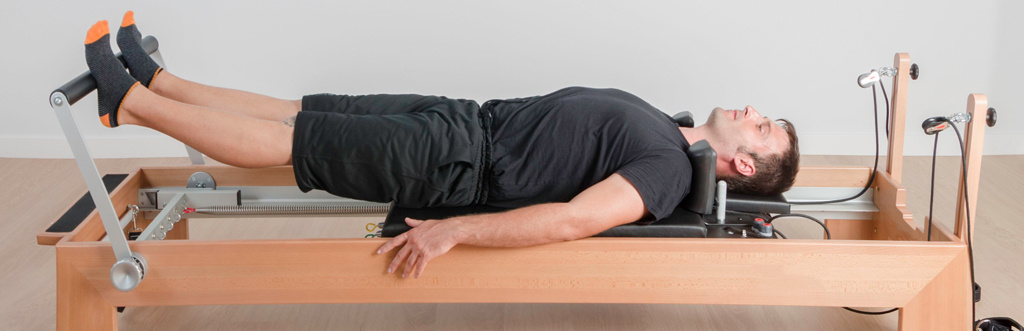 A man using a reformer Pilates machine to exercise