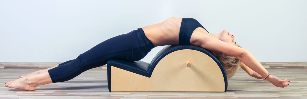 Pilates student using a spine corrector in a Pilates studio