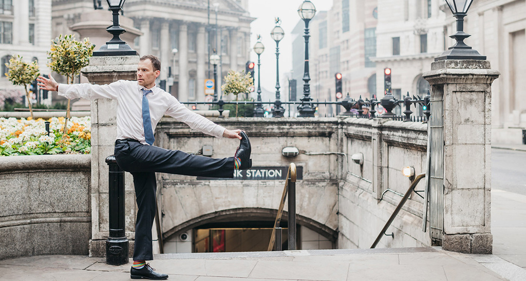Creator of Yogibanker Scott Robinson performing a yoga pose in a suit