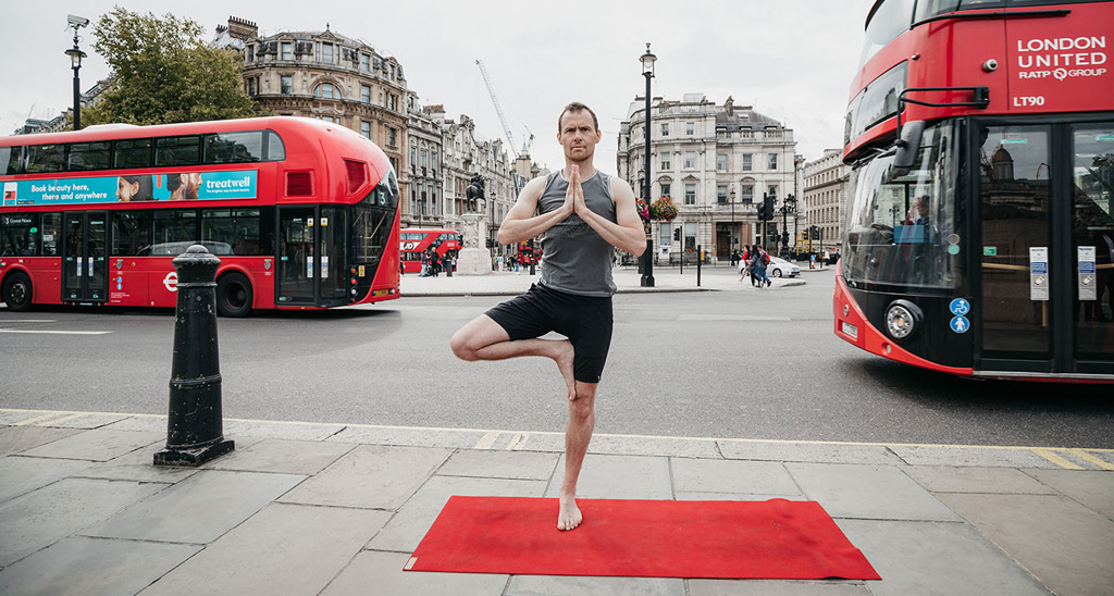 Creator of Yogibanker Scott Robinson performing the tree pose in London