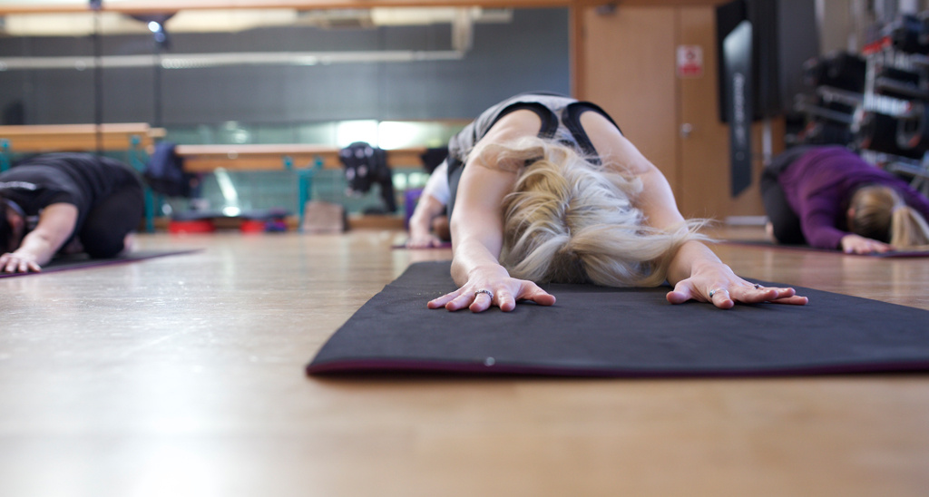 Students performing child's pose in a yoga class
