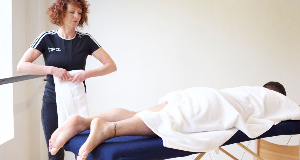 Client lying on a sports massage bed