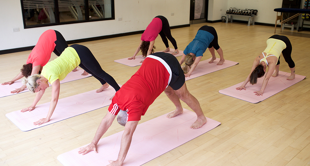 A mixed ability class performing the yoga pose downward-facing dog