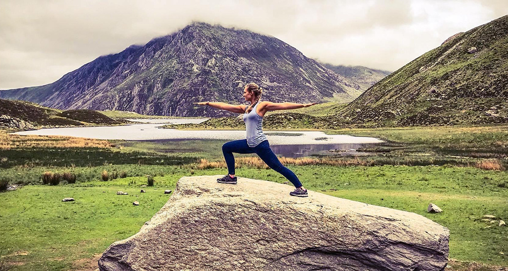 HFE graduate Aneliese Foxwell performs the Warrior 2 yoga pose