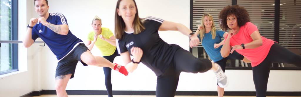 Exercise to music instructor performing a side kick