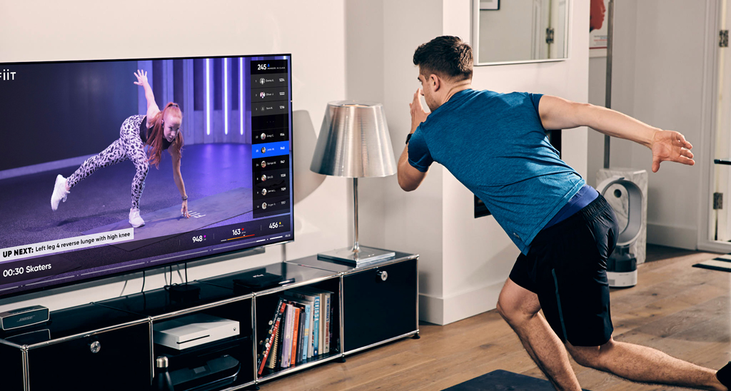 A man using an on-demand fitness platform to workout at home