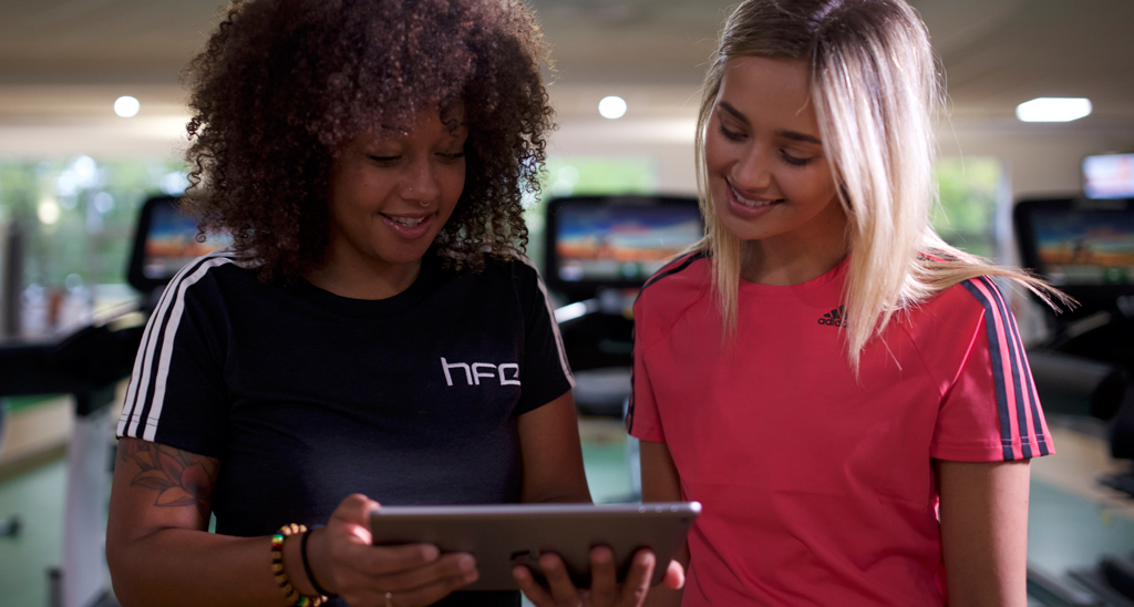 HFE personal training tutor and a student using an iPad
